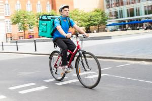The Gig Economy: Courier On Bicycle Delivering Food In City